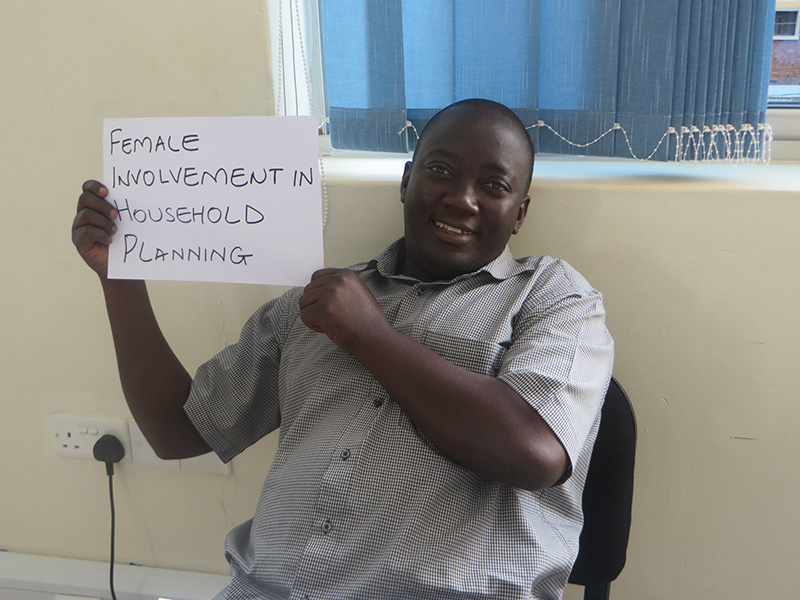 "Man holding card that says ""Female involvement in household planning"""