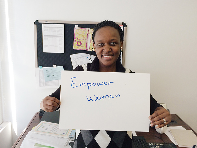 """Woman holding card that says """"Empower women"""""""