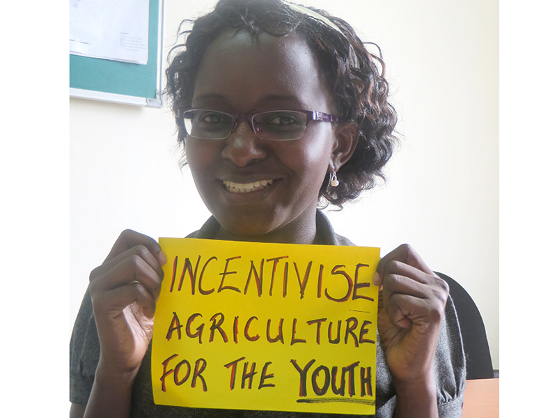 "Woman holding card that says ""Incentivise Agriculture for the youth"""