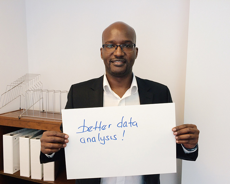 """Man holding card that says """"Better data analysis"""""""