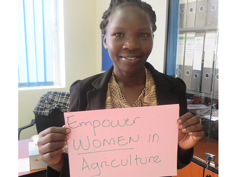 """Woman holding card that says """"Empower women in agriculture"""""""