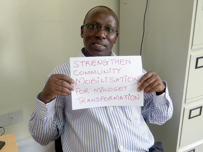 "Man holding card that says ""Strengthen Community Mobilisation for Mindset Transformation"""