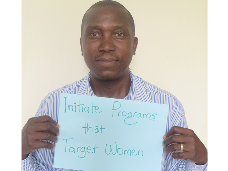 """Man holding card that says """"Initiate programs that target women"""""""