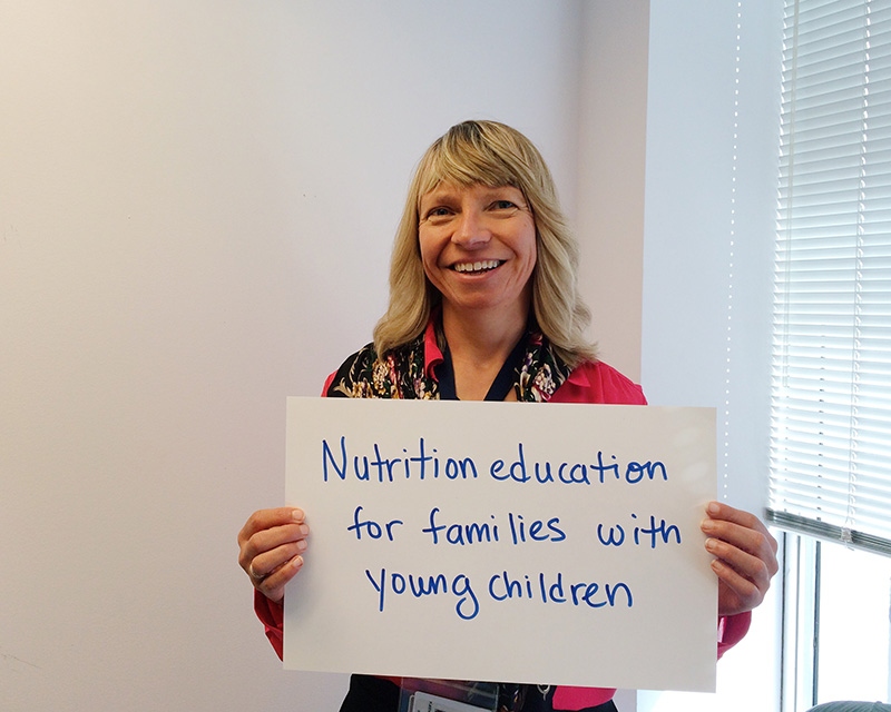 """Woman holding card that says """"Nutrition education for families with young children"""""""