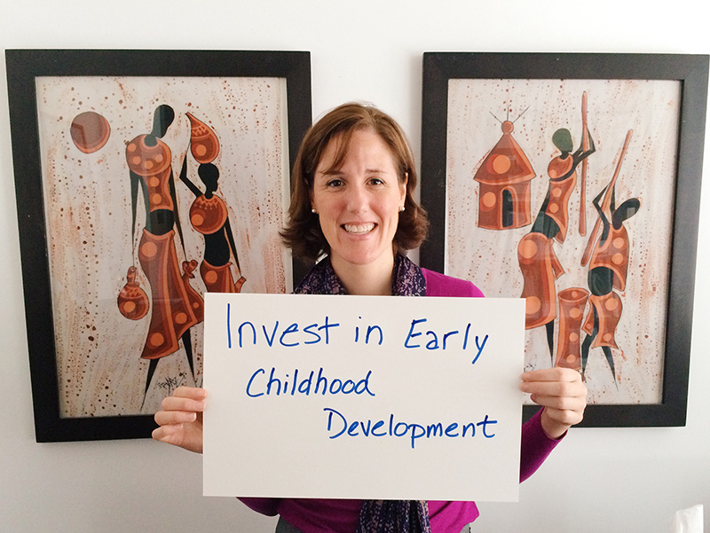 """Woman holding card that says """"Invest in early childhood development"""""""