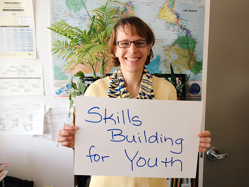 """Woman holding card that says """"Skills building for youth"""""""