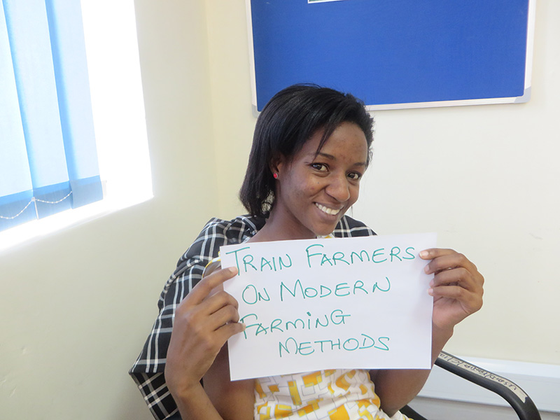"Woman holding card that says ""Train farmers on modern farming methods."""
