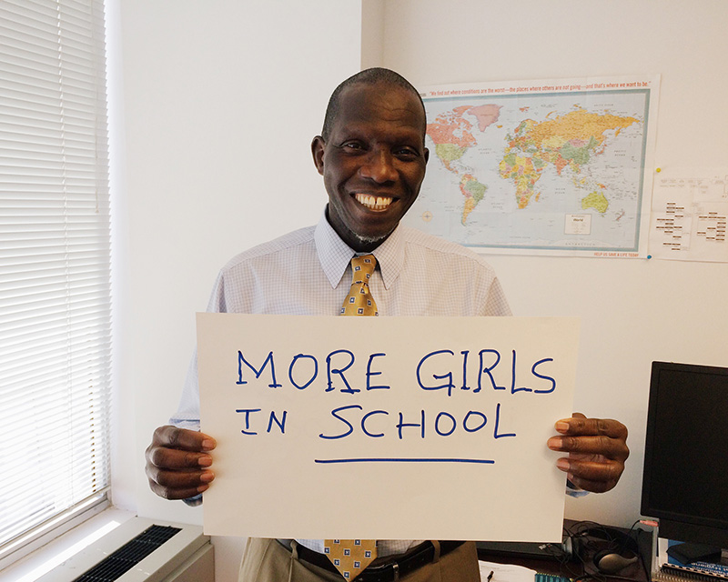"""Man holding card that says """"More girls in school"""""""