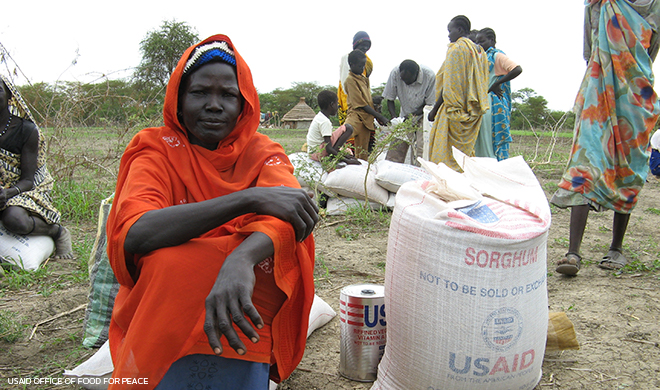woman sits next to USAID bag of supplies while other people stand and walk nearby