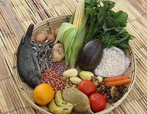 Basket full of variety of foods like fish, grains, and leafy vegetables.