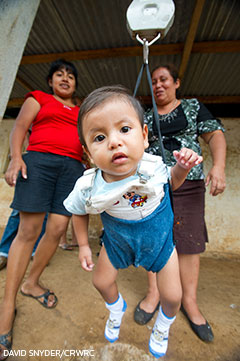 a baby gets weighed in Guatemela