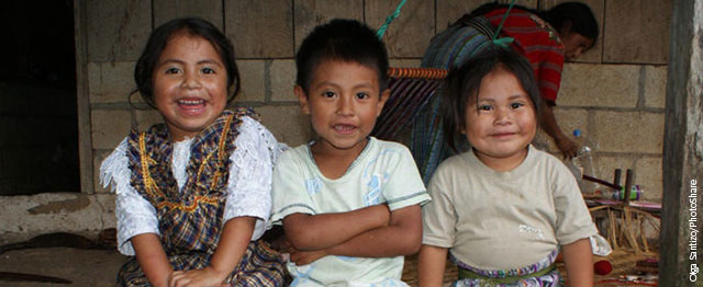 Three smiling children in Guatemala sit in a row.