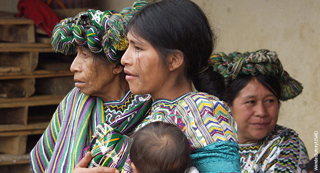 One elderly woman, one middle-aged woman, and a younger woman holding a baby in Guatemala.