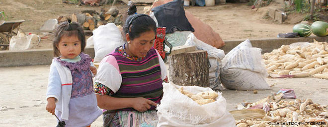 A woman prepares corn as a young child watches in Patzún, Chimaltenango, Guatemala.