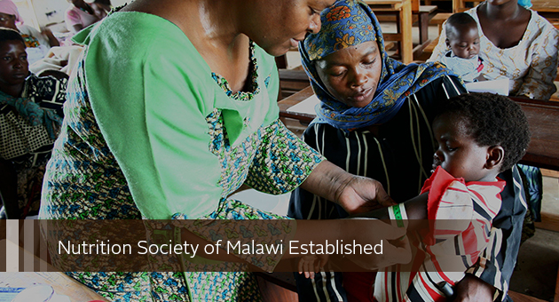 Nutrition Society of Malawi Established. photo of staff measuring arm of child in mother's lap