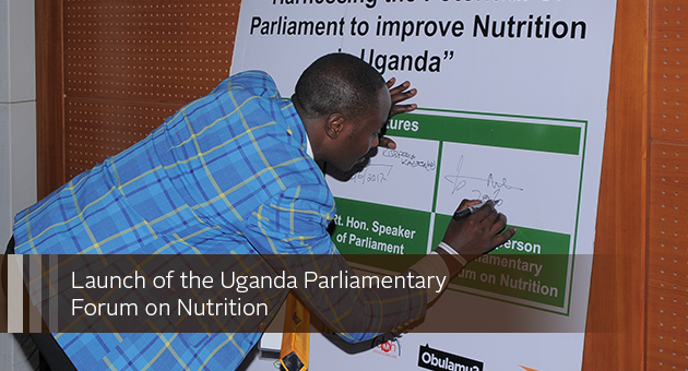 Launch of the Uganda Parliamentary Forum on Nutrition. Photo of a person signing a board.
