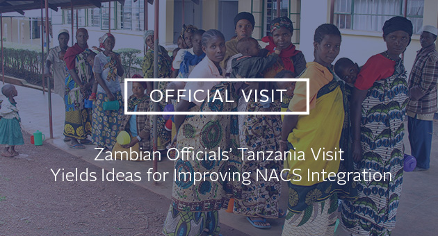 Official Visit: Zambian Officials' Tanzania Visit Yields Ideas for Improving NACS Integration. Photo of women and children waiting in line for a clinic
