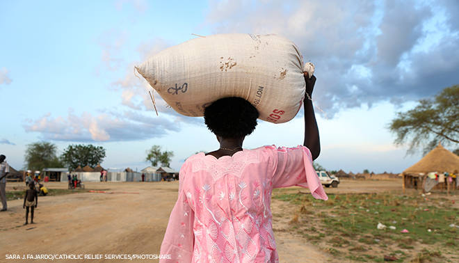 woman carrying bag of supplies on head