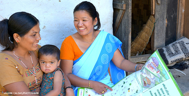 health worker teaching nutrition topics to mother with baby