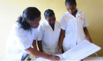 Photo of nurses in Mozambique looking at a health register.