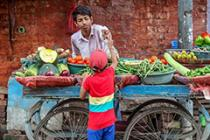 boy buying produce at a cart
