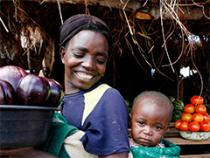 photo of smiling woman carrying bucket of produce with baby on her back