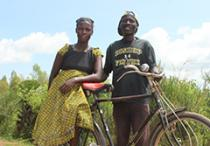 Man and woman with bike next to field