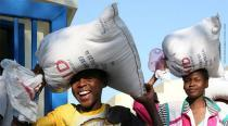 Two women carry bags of supplies on their heads.