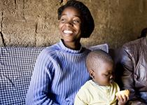 smiling mother holding child eating fruit