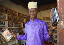 a video merchant holds DVDs of Ngoma Ya Roho