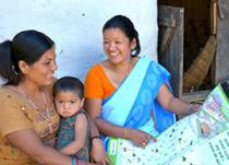 health worker showing mother with baby a learning aid