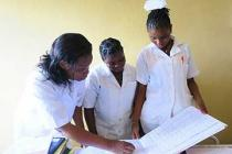 Image of nurses in Mozambique looking at a health register.