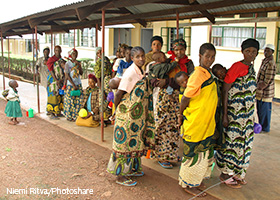 group of people waiting in line outside a clinic